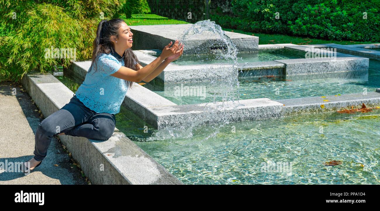 Niña jugando con fuente de agua - Das Mädchen mit Brunnenwasser spielt - Ragazza che gioca con l'acqua della Fontana Imagen De Stock