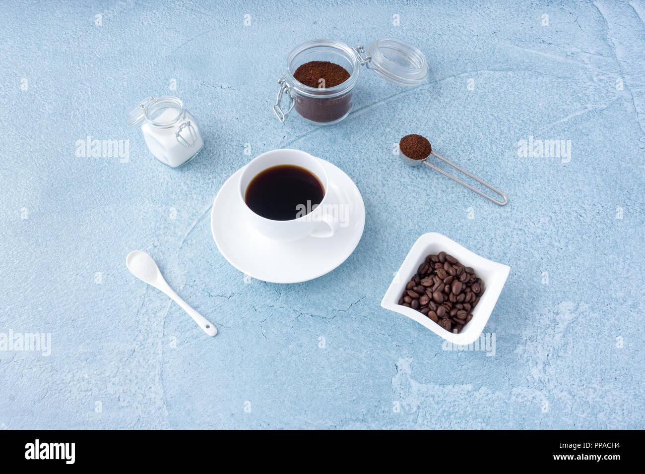 Taza llena de café, azúcar, café molido y café en granos azul de fondo concreta. Imagen De Stock