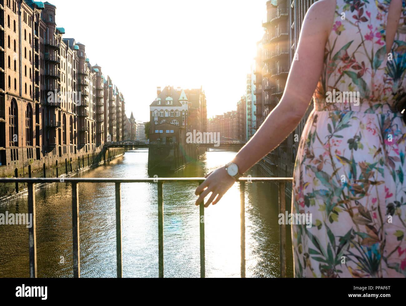 Vista trasera parcial de la mujer en el puente contra edificios históricos y canal Foto de stock