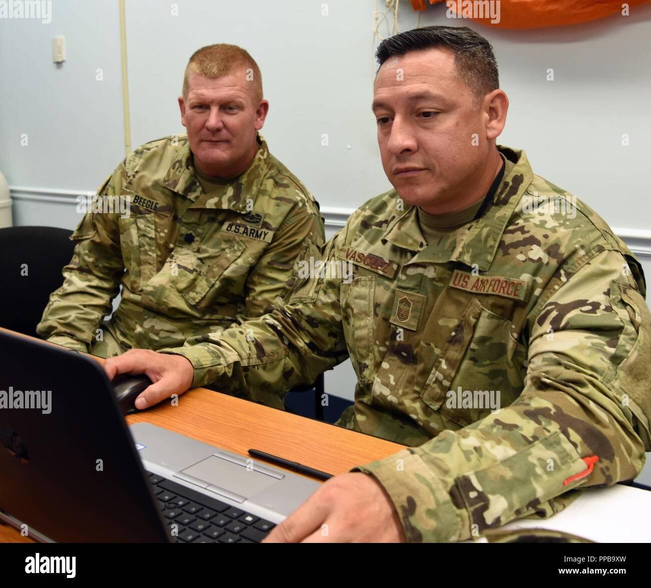 El Teniente Coronel del Ejército de EE.UU Zane Beegle, izquierda, personal de ejercicio (STAFFEX) 18-5 J-4 dirección de logística con el planificador de West Virginia, la Guardia Nacional del Ejército y la Fuerza Aérea de los EE.UU. Master Senior Sgt. Andy Vasquez, Noveno J-4 de la Fuerza Aérea planner, revise los requerimientos de logística para el ejercicio escenario, el 14 de agosto de 2018, la base de la fuerza aérea Shaw, S.C. El J-4 dirección está encargado de formar Planes de logística y servicios, que incluyen la coordinación y supervisión del suministro, las operaciones de mantenimiento, implementación y distribución, ingeniería, servicios de salud, anticonceptivos orales, servicio de alimentos, y otros logístico necesario operativamente sup Foto de stock