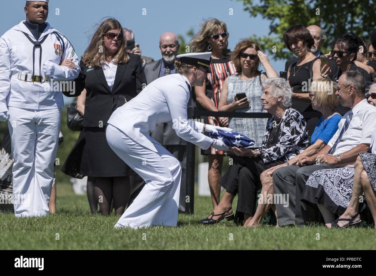 El Teniente de la Marina estadounidense Danielle Garbarino, comandante de las tropas de la Guardia ceremonial, La Marina de los Estados Unidos, presenta la bandera de los EE.UU a Lucy Liebenow honores durante todo el funeral de su marido, el Teniente Comandante de la Marina estadounidense William Liebenow en la sección 62 del Cementerio Nacional de Arlington, Arlington, Virginia, 23 de agosto de 2018. El 7 de agosto de 1943, una patrulla patroneado Liebenow barco torpedo para rescatar a los marineros de PT-109 que habían sobrevivido a varios días en inhóspitas islas tras un destructor japonés había embestido su barco, matando a dos miembros de la tripulación. Entre las personas rescatadas fue la bunkmate Liebenow, John F. Kennedy, entonces de 26. Por sus actos de h Foto de stock