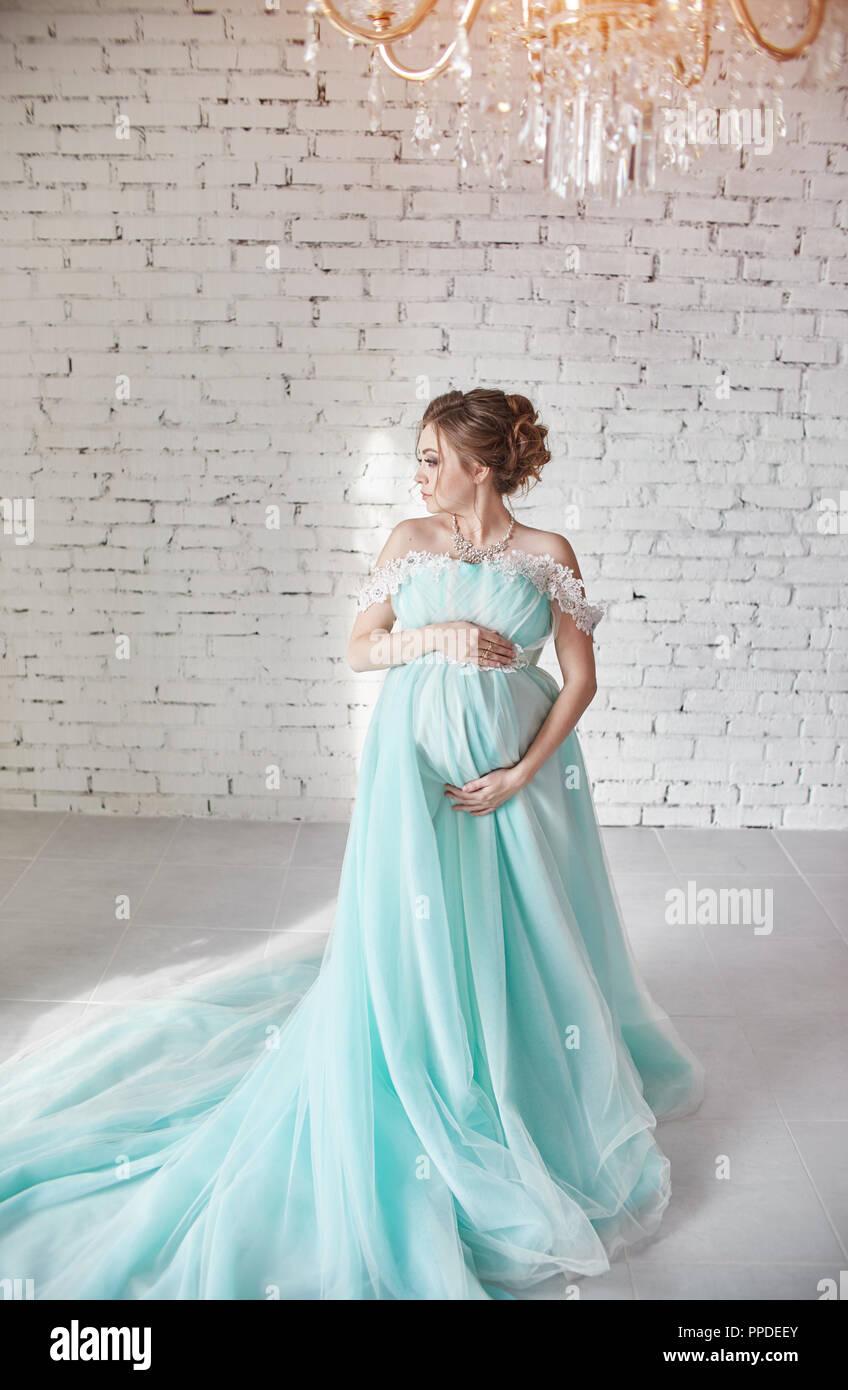 395f3fed7 Feliz mujer embarazada en vestido de noche largo de tocar las manos del  vientre. Esperando