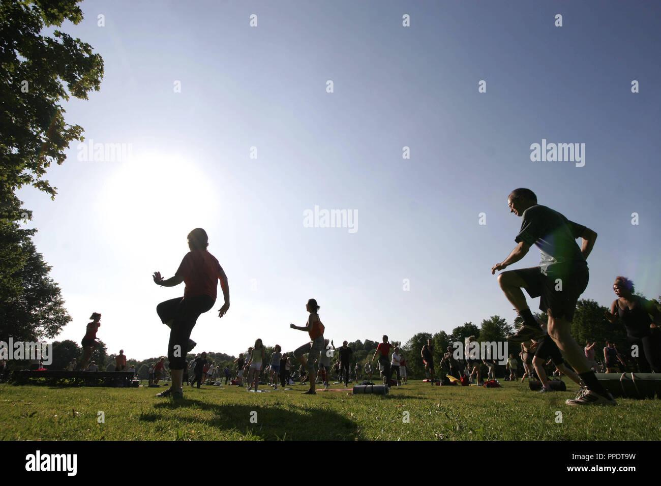 Los atletas moverse bajo la orientación de un entrenador en el gimnasio en el 'Park', un programa de acondicionamiento físico de la ciudad de Munich, que se celebra diariamente a las 18.00 Reloj en determinados parques en Munich. Imagen De Stock