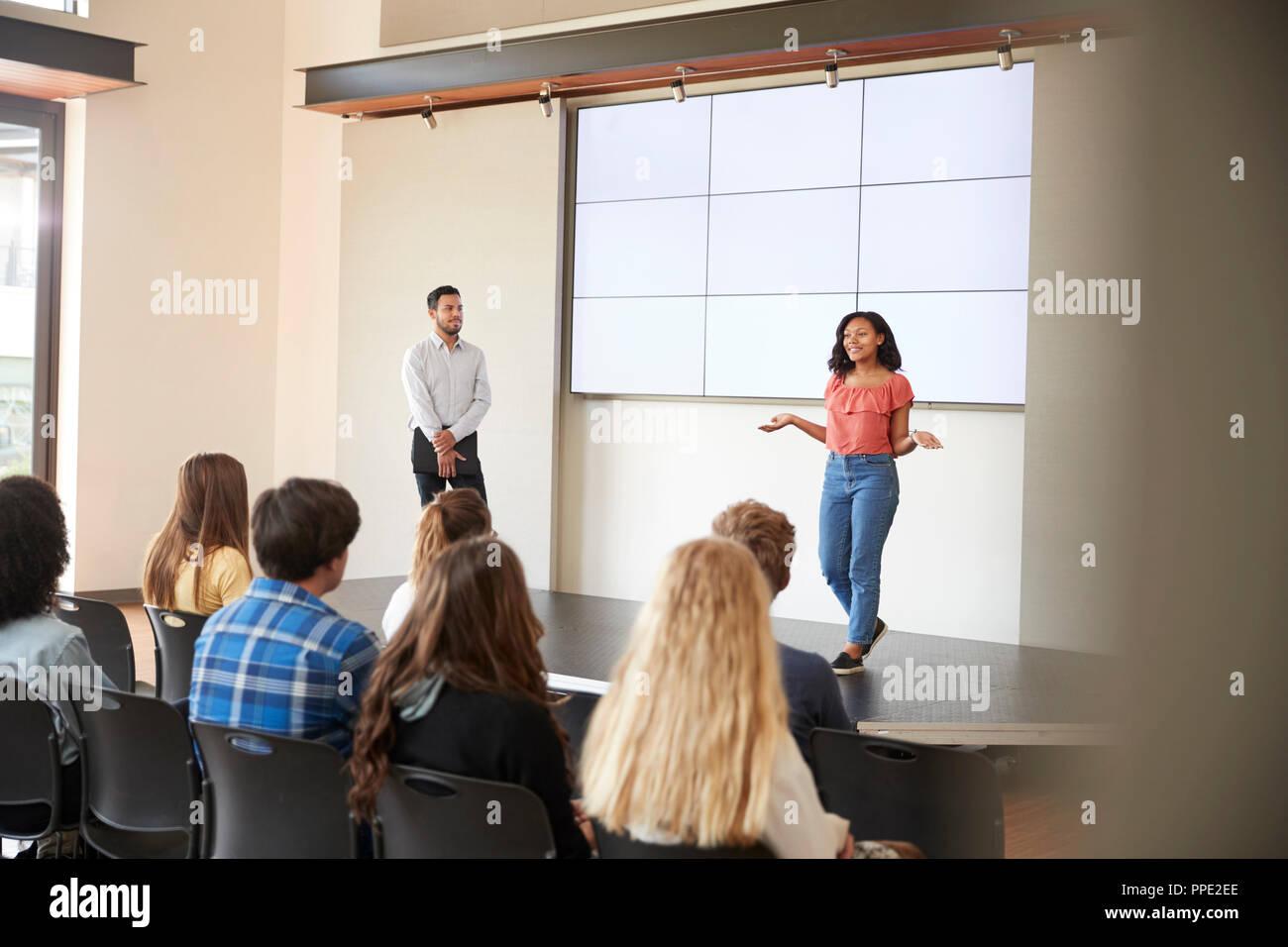 Estudiante femenina dando Presentación a clase en la escuela en la parte delantera de la pantalla Foto de stock