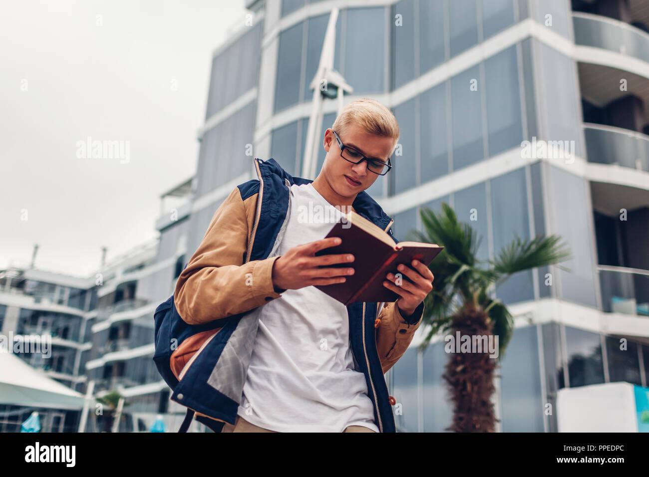 Estudiante universitario con mochila libro de lectura caminando por el moderno hotel de playa tropical. Joven estudiando afuera en otoño lluvioso día Imagen De Stock