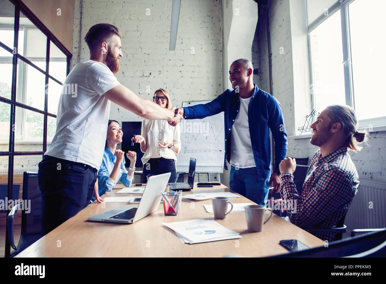 Nuevos socios comerciales. Jóvenes colegas moderno en smart ropa casual se estrechan las manos y sonriendo mientras está sentado en la oficina creativa. Imagen De Stock