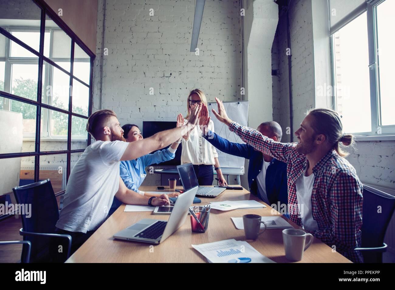 Feliz éxito multirracial equipo empresarial dando una alta cincos gesto como se ríen y alegrar su éxito. Imagen De Stock