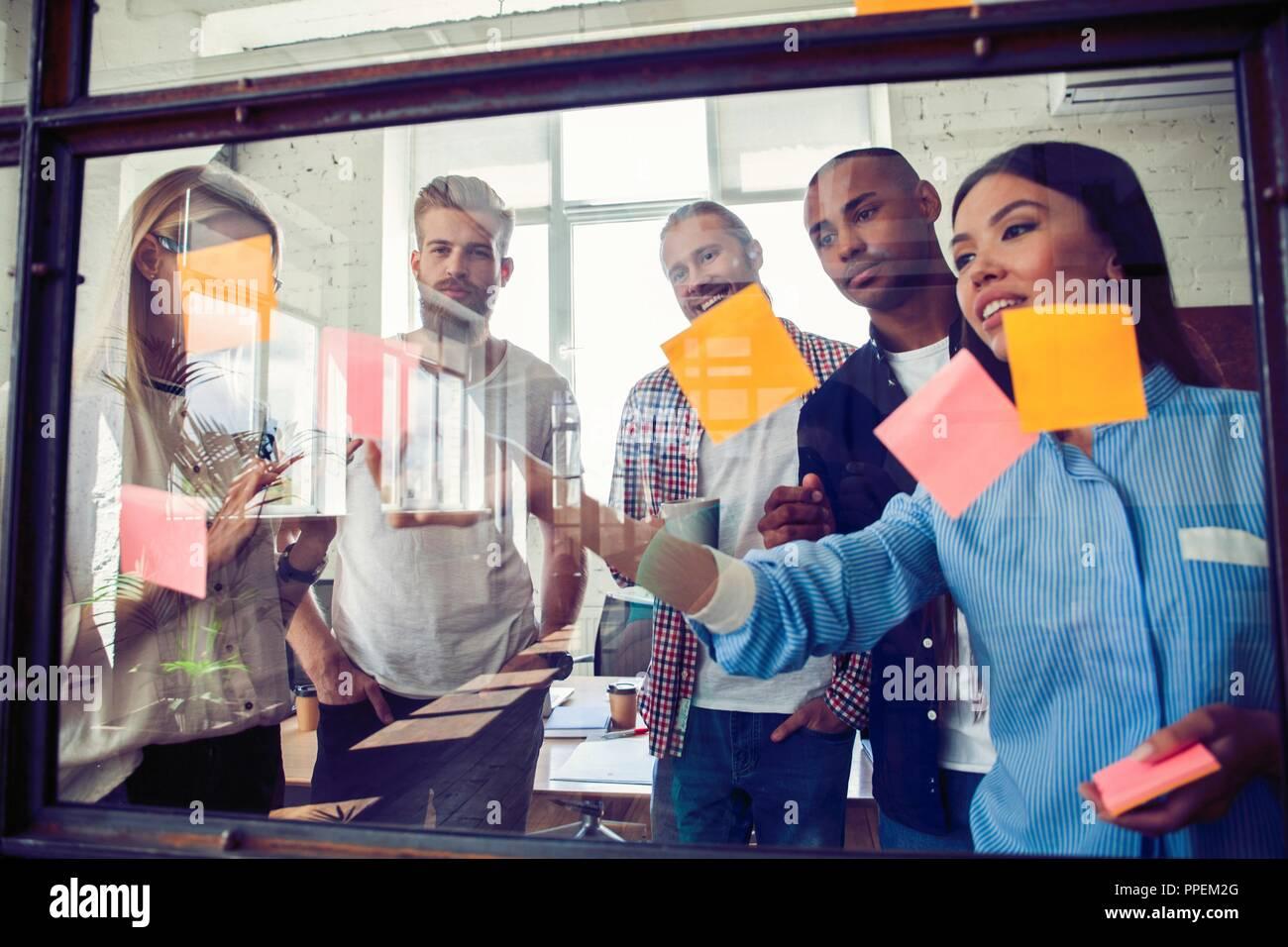 Los empresarios reunidos en la oficina y utilizar post-it Notes para compartir la idea. Concepto de lluvia de ideas. Nota adhesiva en pared de vidrio Imagen De Stock