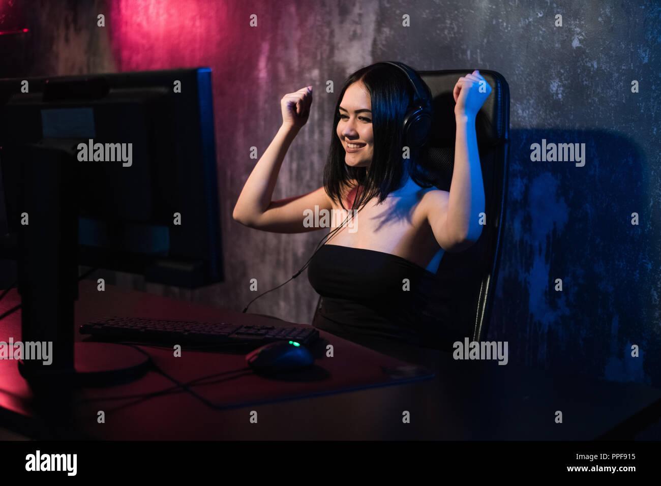 Retrato de una joven niña alegre que se alegra después de ganar un juego de video, - celebrando ganando en emociones jugando concepto. Foto de stock