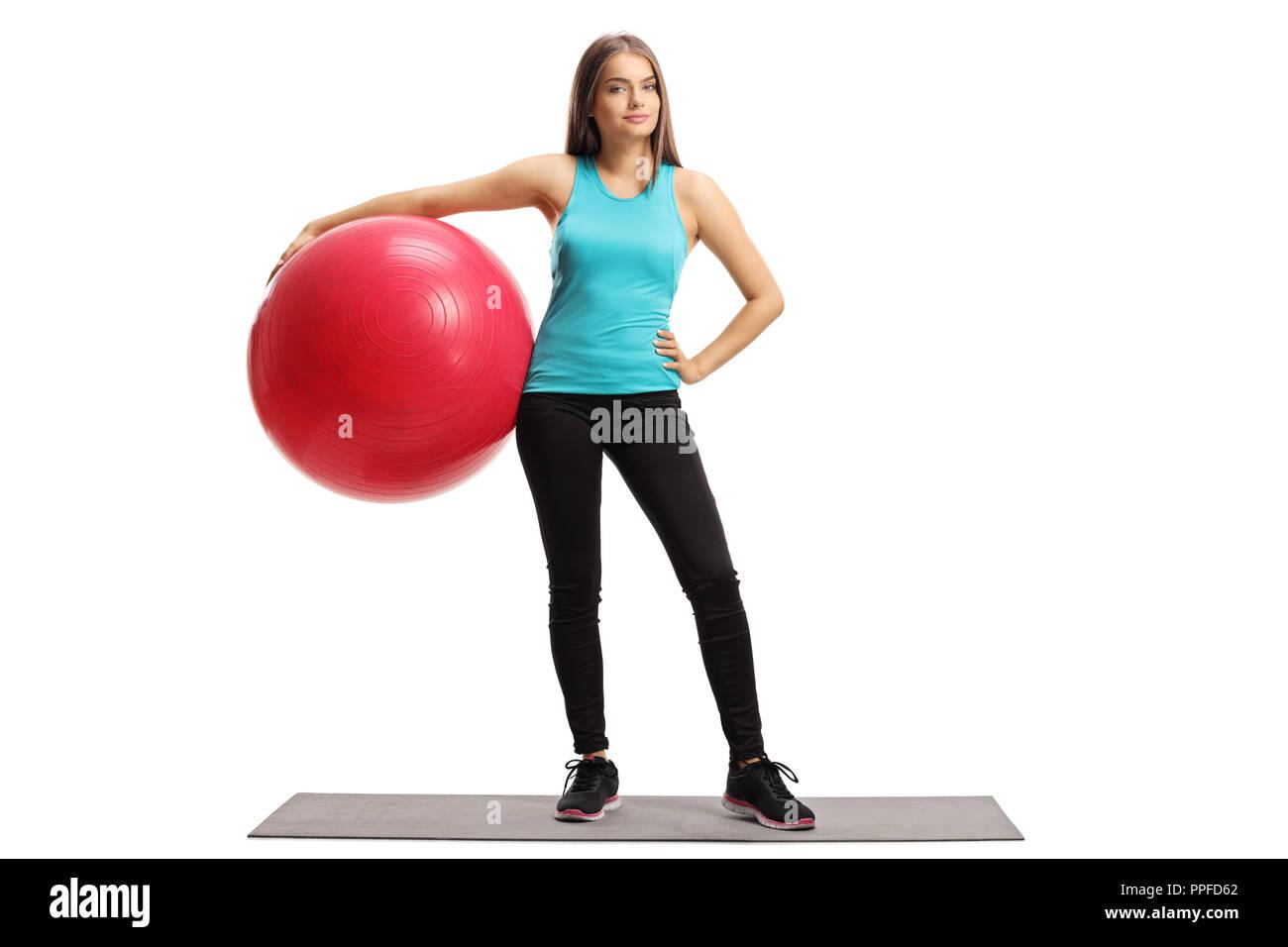 Longitud total retrato de una mujer joven con una pelota de pilates de pie  sobre una d27d29732cd2