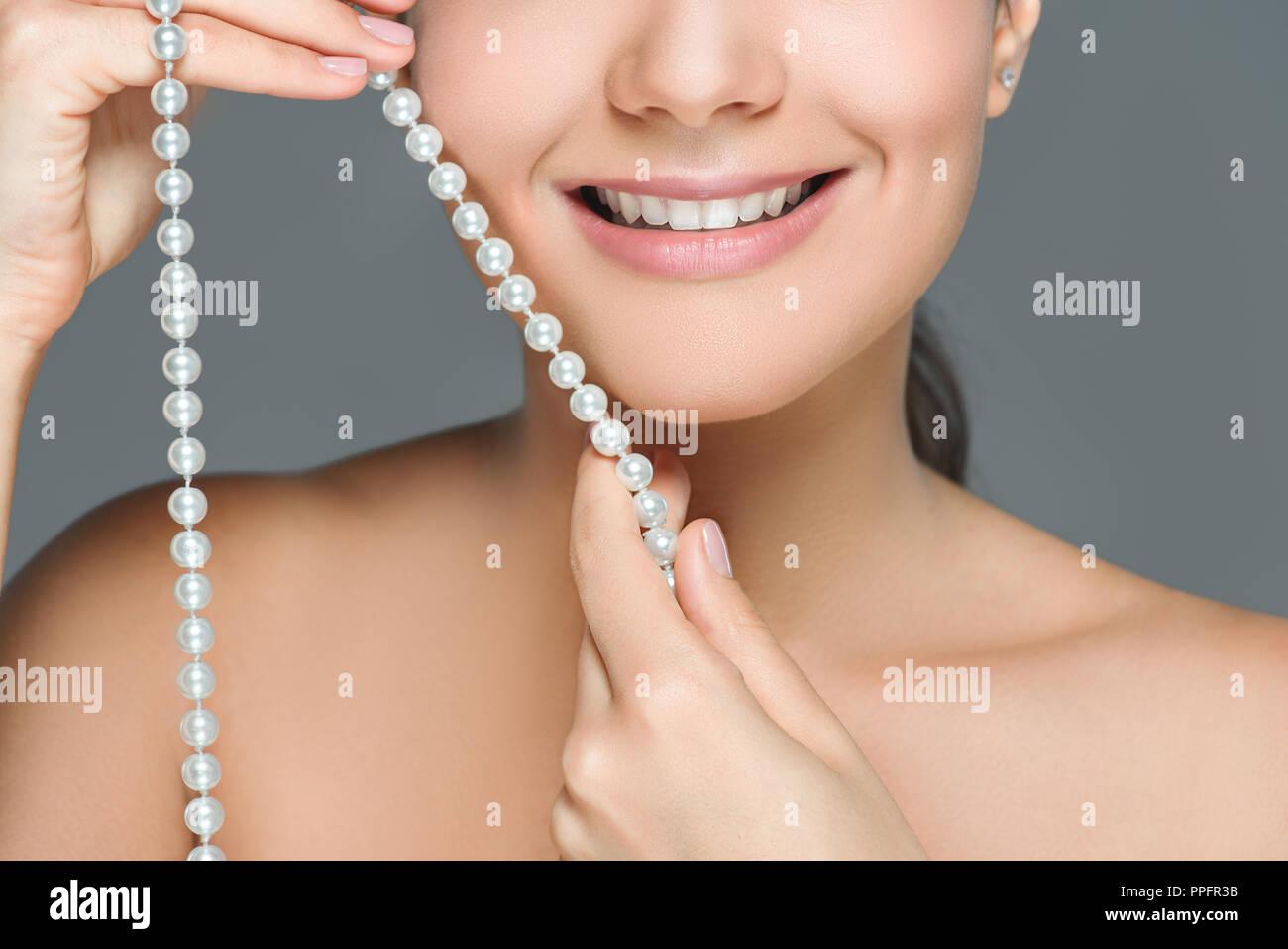 2eecb12b436c Captura recortada de mujer sonriente con dientes blancos y perlas en manos  aisladas sobre gris Imagen
