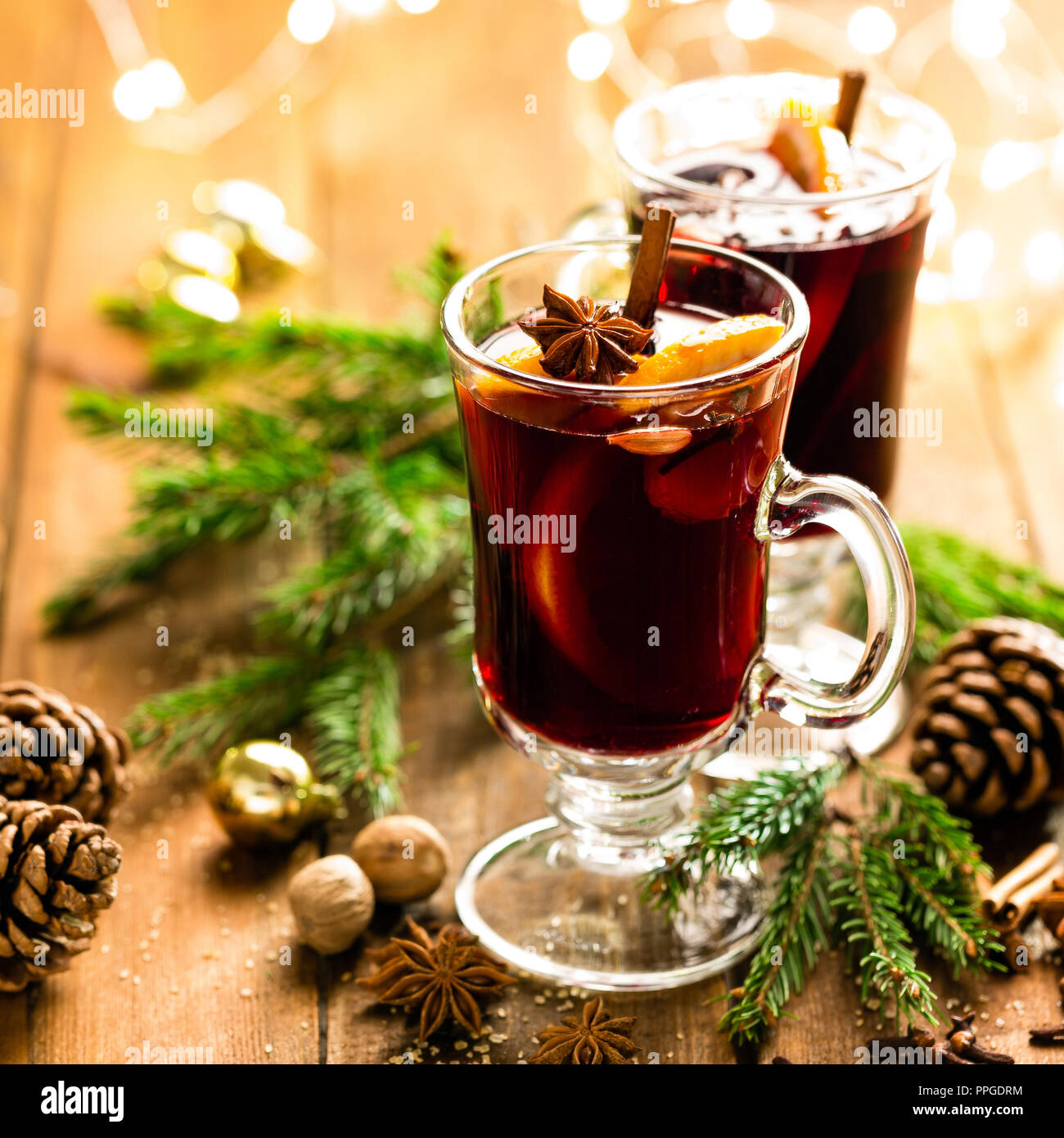 Navidad vino tinto especiado con especias y naranjas en una mesa de estilo rústico de madera. Bebida caliente tradicional en Navidad Foto de stock