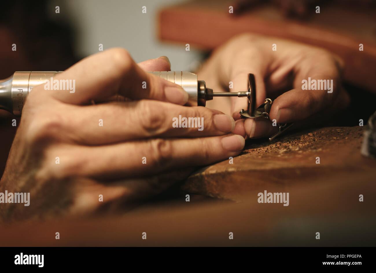 43016a13e413 Manos de mujeres jeweler pulir un pedazo de joyería con Máquina  esmeriladora. Goldsmith haciendo una