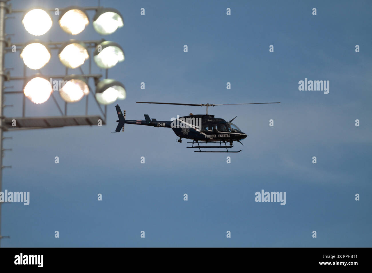 SEGURIDAD. Aeronave, el helicóptero de la policia estatal sobrevolando cerca de las lamparas del Estadio Sonora , durante el primer dia de acción en la Foto de stock