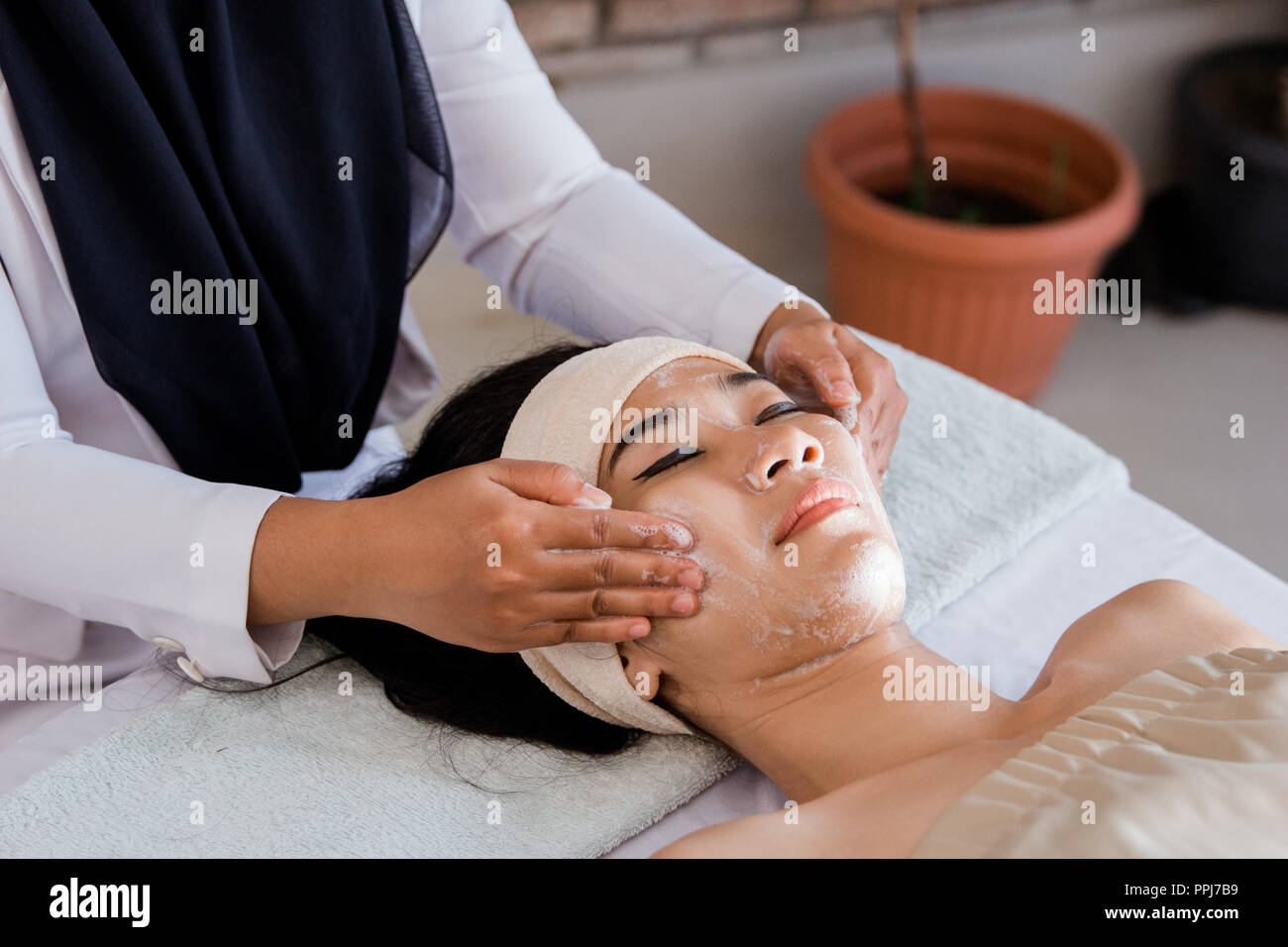 Mujer joven disfrutando de masaje con crema de máscara Imagen De Stock