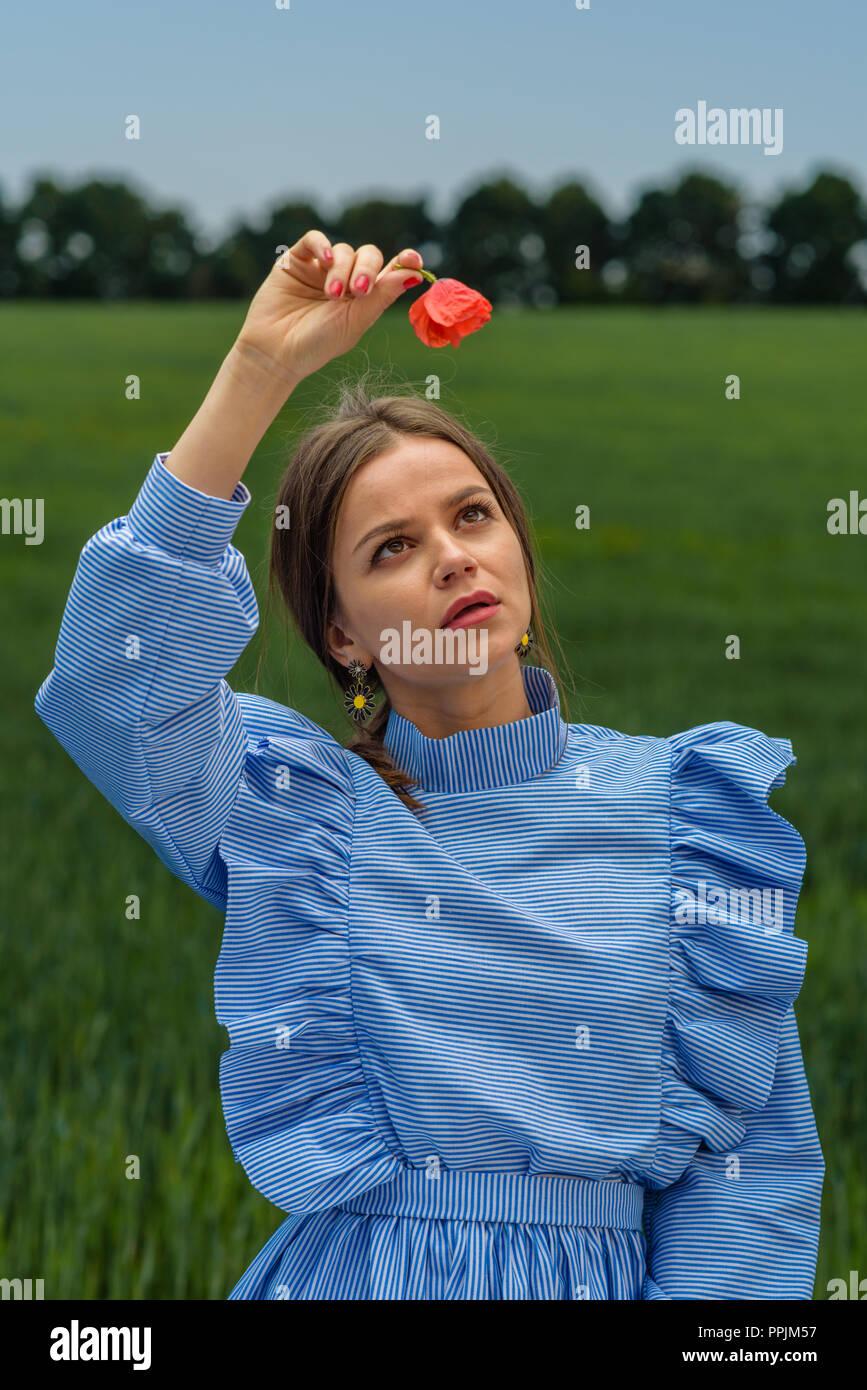 2445f6ca23 Mujer joven en traje a rayas azules y blancas sosteniendo una flor de  amapola roja sobre
