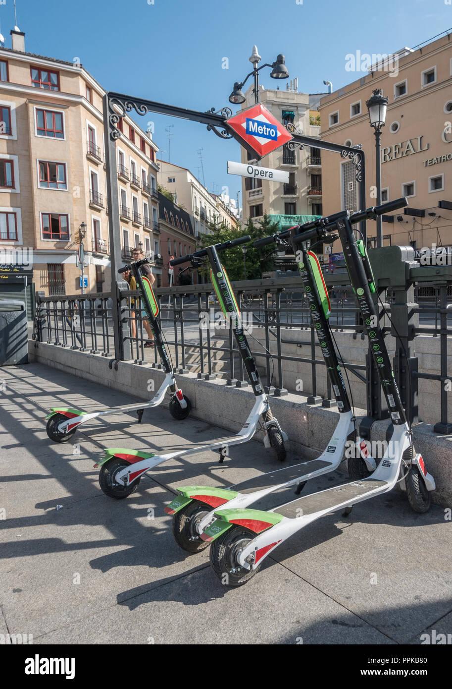 Scooters eléctricos cal estacionado en la Plaza de Isabel II, Madrid, España. Entrada de Metro Ópera de fondo. Cal-S scooters llegó a Madrid, en agosto de 2018. Imagen De Stock