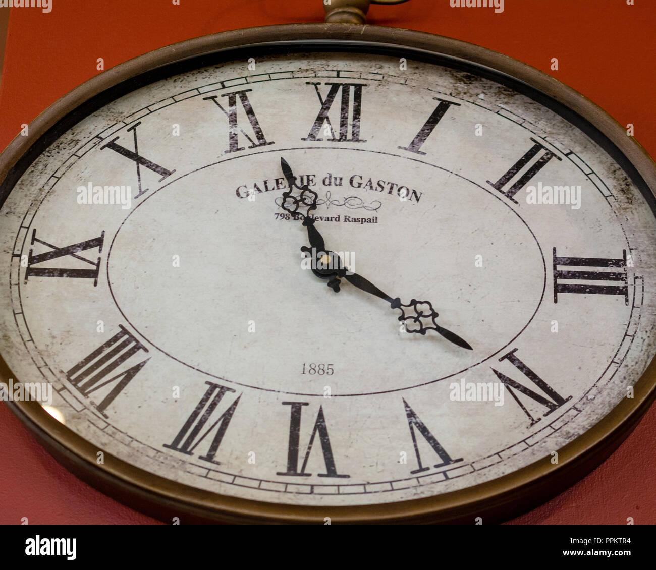 1885 Galerie du Gaston Oval Reloj de pared en una pared roja, marcando once horas y veinte minutos Foto de stock