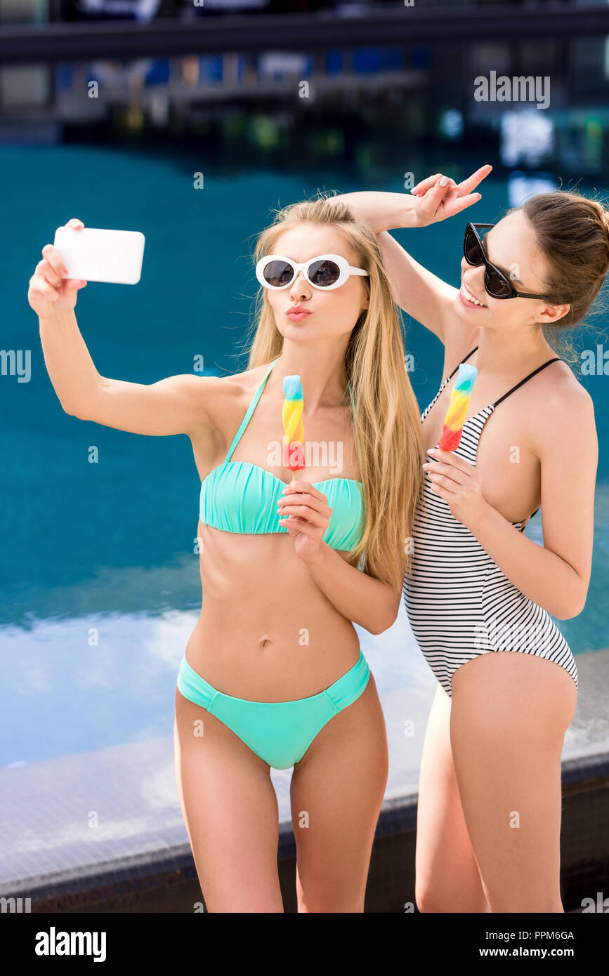 bb82699a2 Hermosas jóvenes en traje de baño y bikini teniendo selfie con paletas en  la piscina Imagen