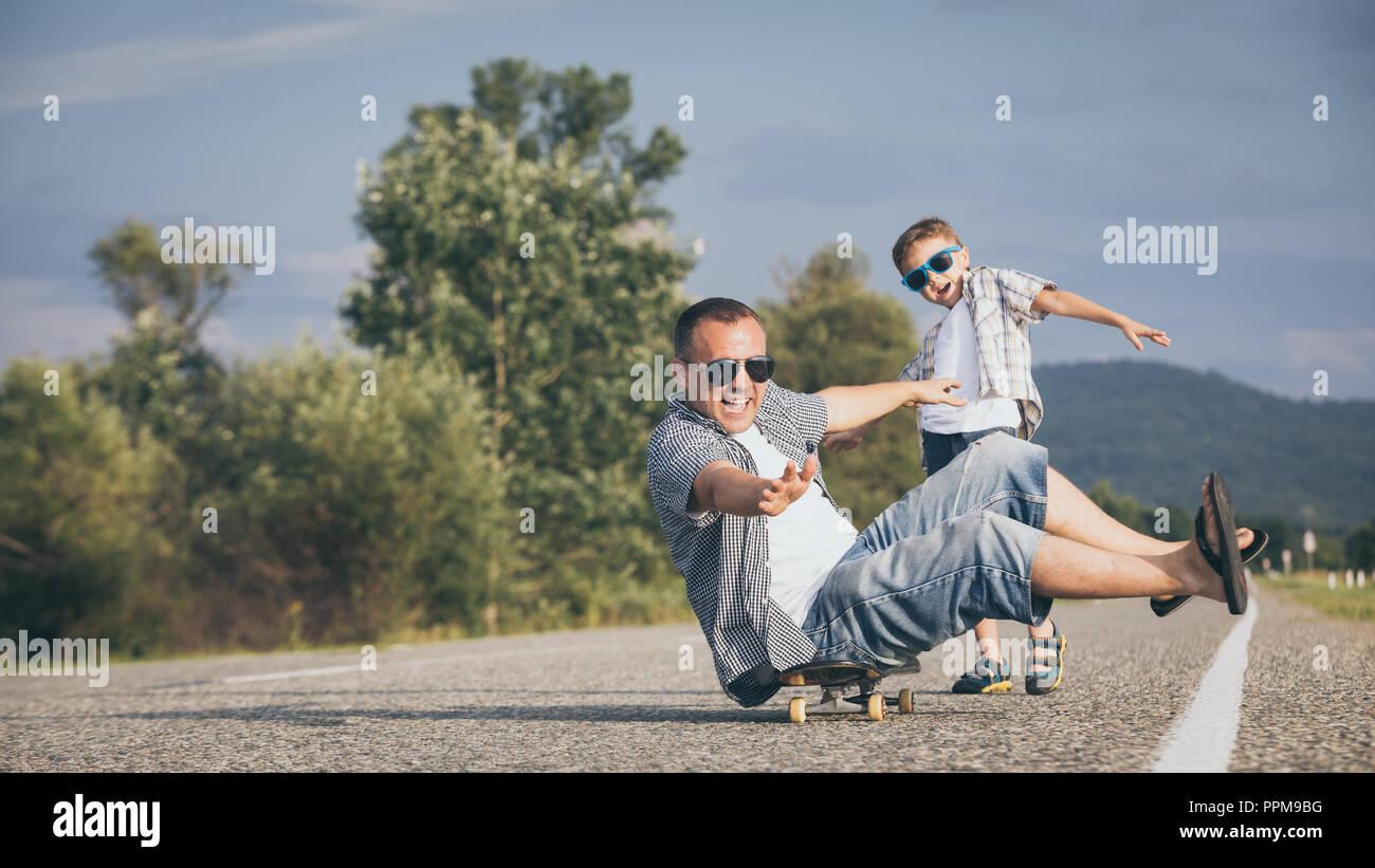 Padre e hijo jugando en la carretera en el día. La gente divirtiéndose al aire libre. Concepto de ambiente familiar. Imagen De Stock
