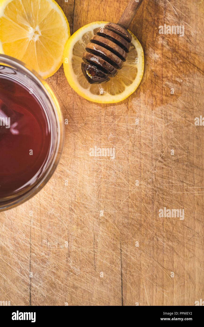 Tratamiento de frío y recursos naturales sobre fondo de madera. Té caliente con limón y miel orgánica. Foto de stock