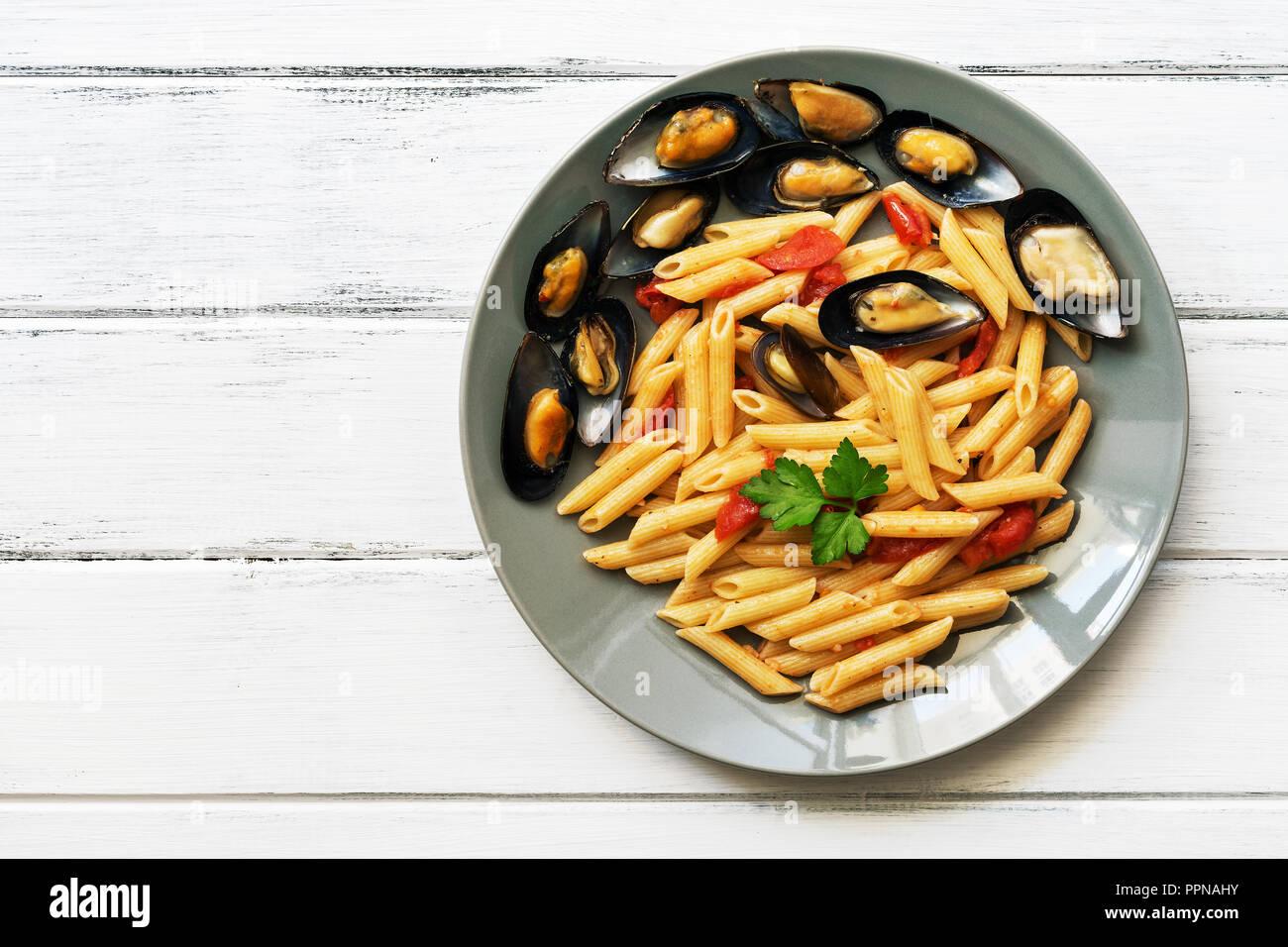 Pasta Penne con mejillones en una mesa de estilo rústico de madera blanca. Vista superior, espacio de copia Imagen De Stock