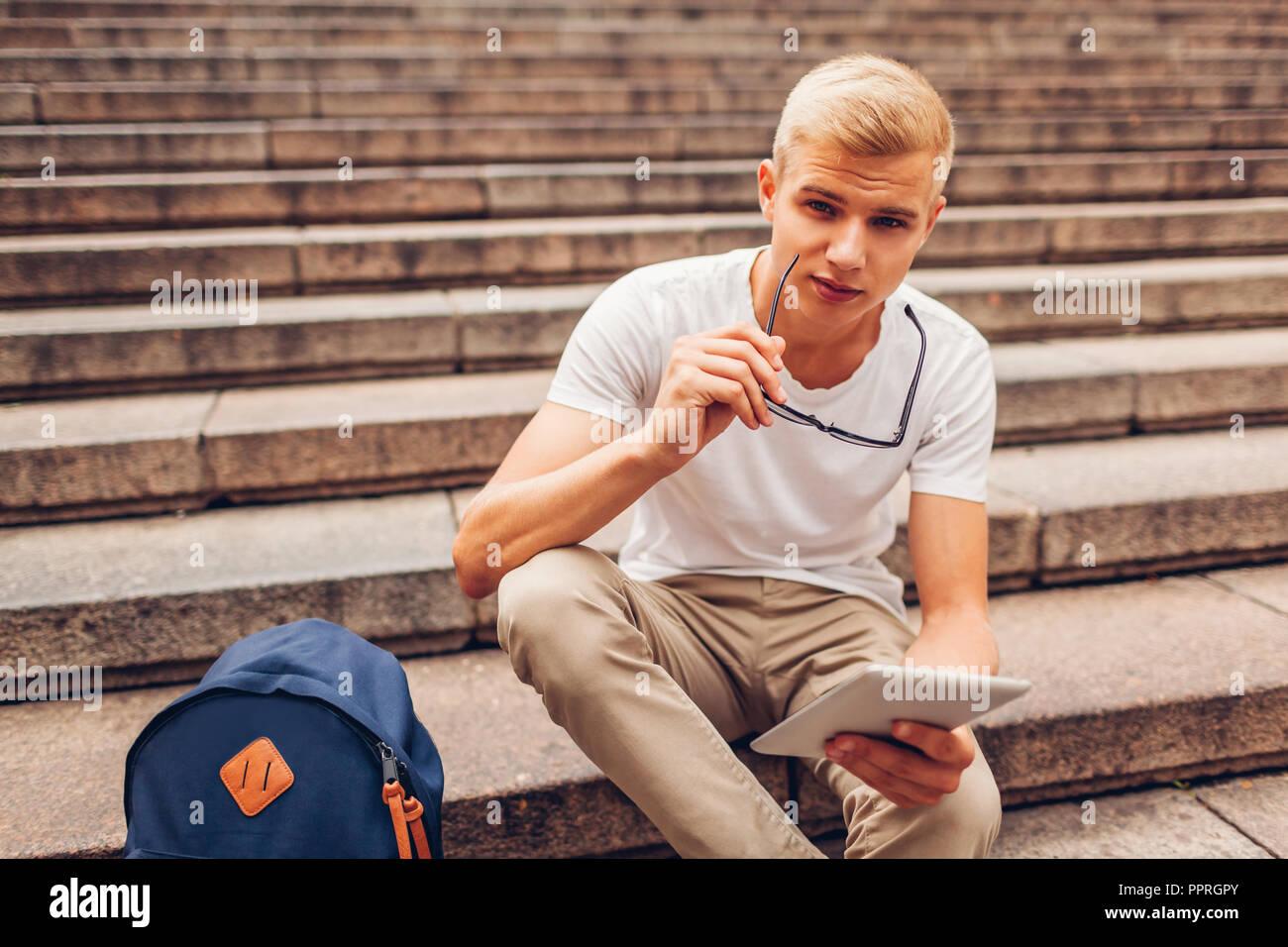 Estudiante universitario con mochila con tablet sentado en las escaleras y manteniendo las gafas. Guy estudiar en el exterior. Concepto de educación Imagen De Stock
