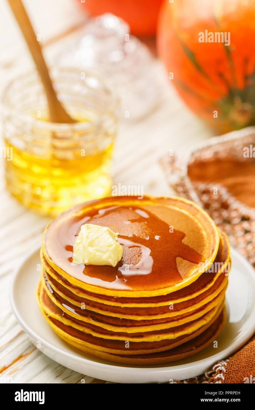 Dulce de calabaza casero panqueques con miel y mantequilla en una placa blanca. Sabroso tradicional desayuno saludable para gourmets. Enfoque selectivo Imagen De Stock