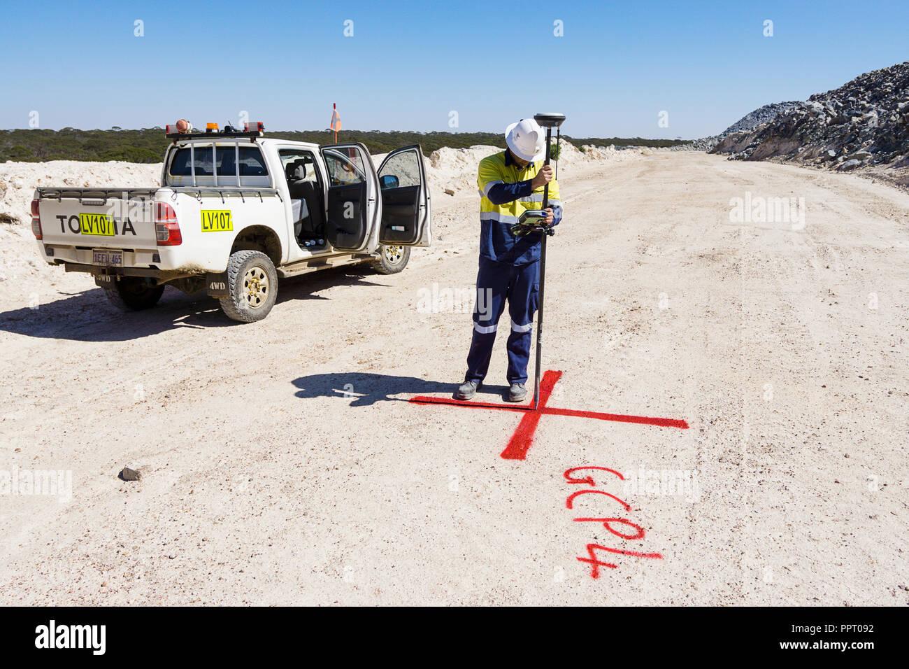Agrimensor marcando el punto de referencia para su uso con zumbido para medir existencias de mineral en una mina de oro en el oeste de Australia. Imagen De Stock