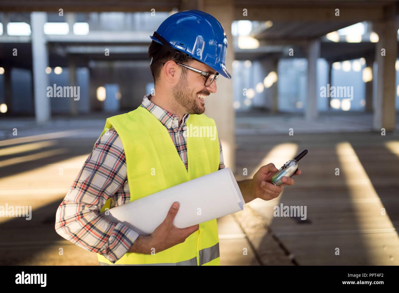 Macho joven arquitecto con planos usando walkie-talkie Imagen De Stock