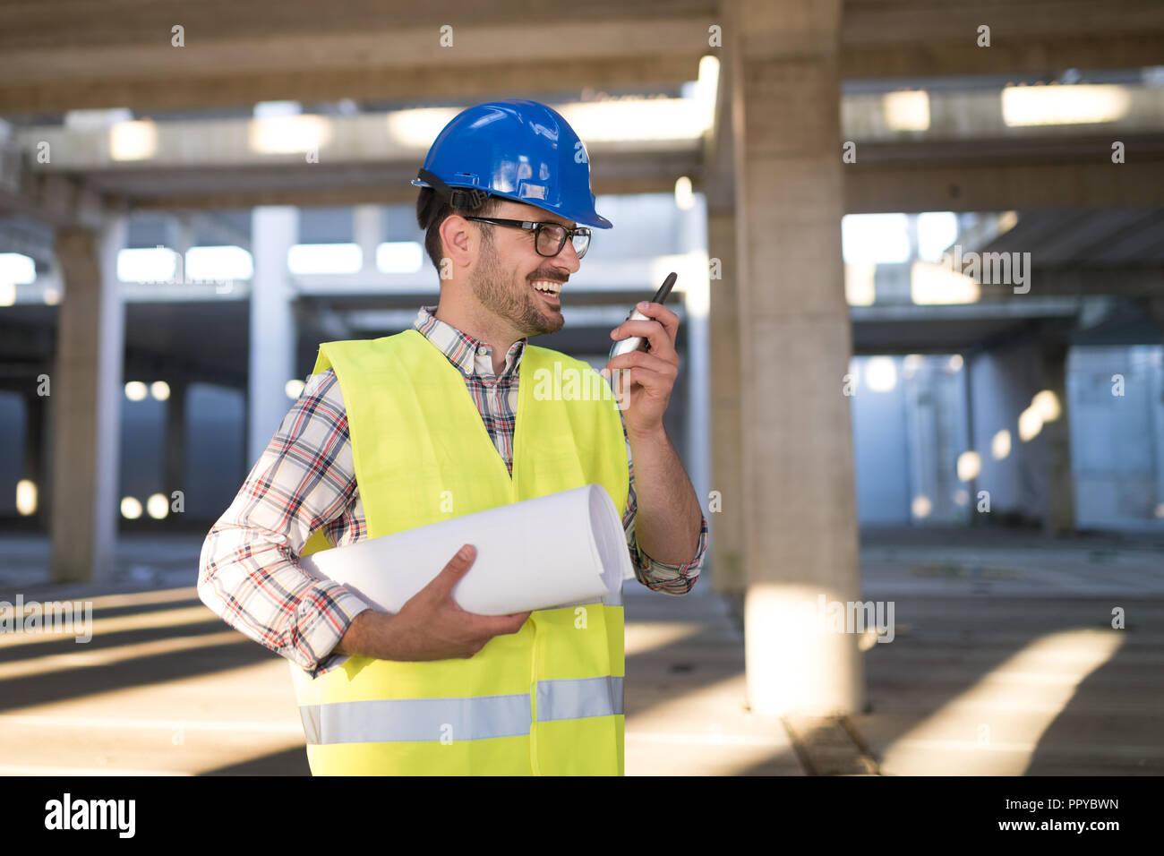 Arquitecto masculino con planos usando walkie-talkie Imagen De Stock