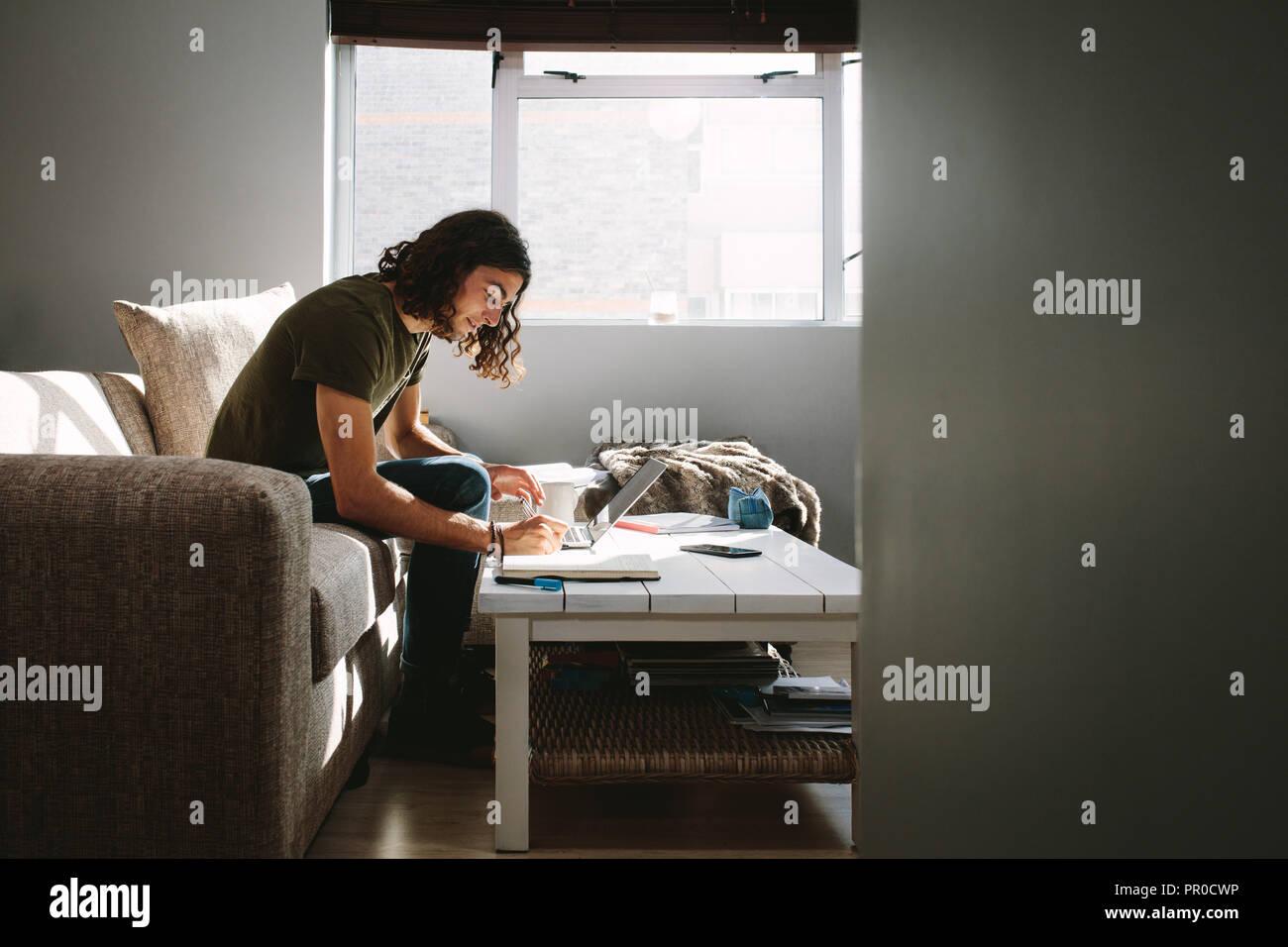 Escribir notas estudiantes sentados en un sofá junto a una ventana en su casa. Joven estudiando con laptop y libros sobre la mesa. Imagen De Stock