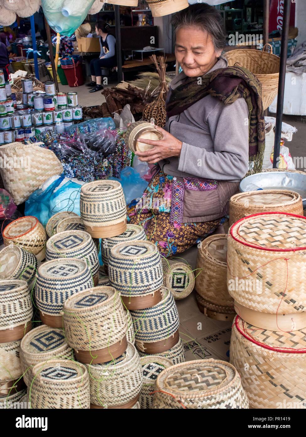 Mujer vendiendo cestas de arroz pegajoso en la zona central de mercado al aire libre, en Luang Prabang, Laos, Indochina, en el sudeste de Asia, Asia Imagen De Stock