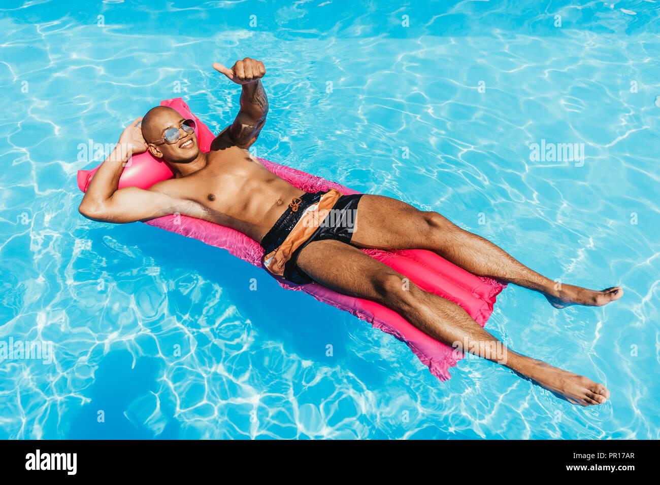 Hombre afroamericano mostrando el pulgar hacia arriba mientras toma el sol sobre un colchón inflable en la piscina Imagen De Stock