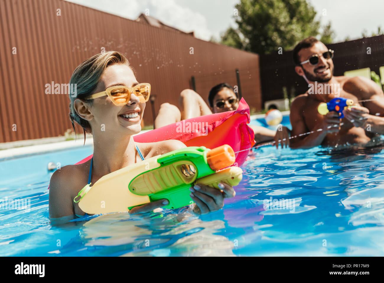 Feliz amigos multiétnica jugando con pistolas de agua de piscina Imagen De Stock