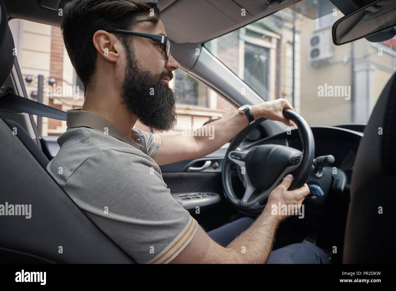 Las personas felices y caras de la ciudad de Concepción. Un hombre barbado positiva conduce su coche por la ciudad mientras sonríe. Disfrutando cada día momentos simples Imagen De Stock