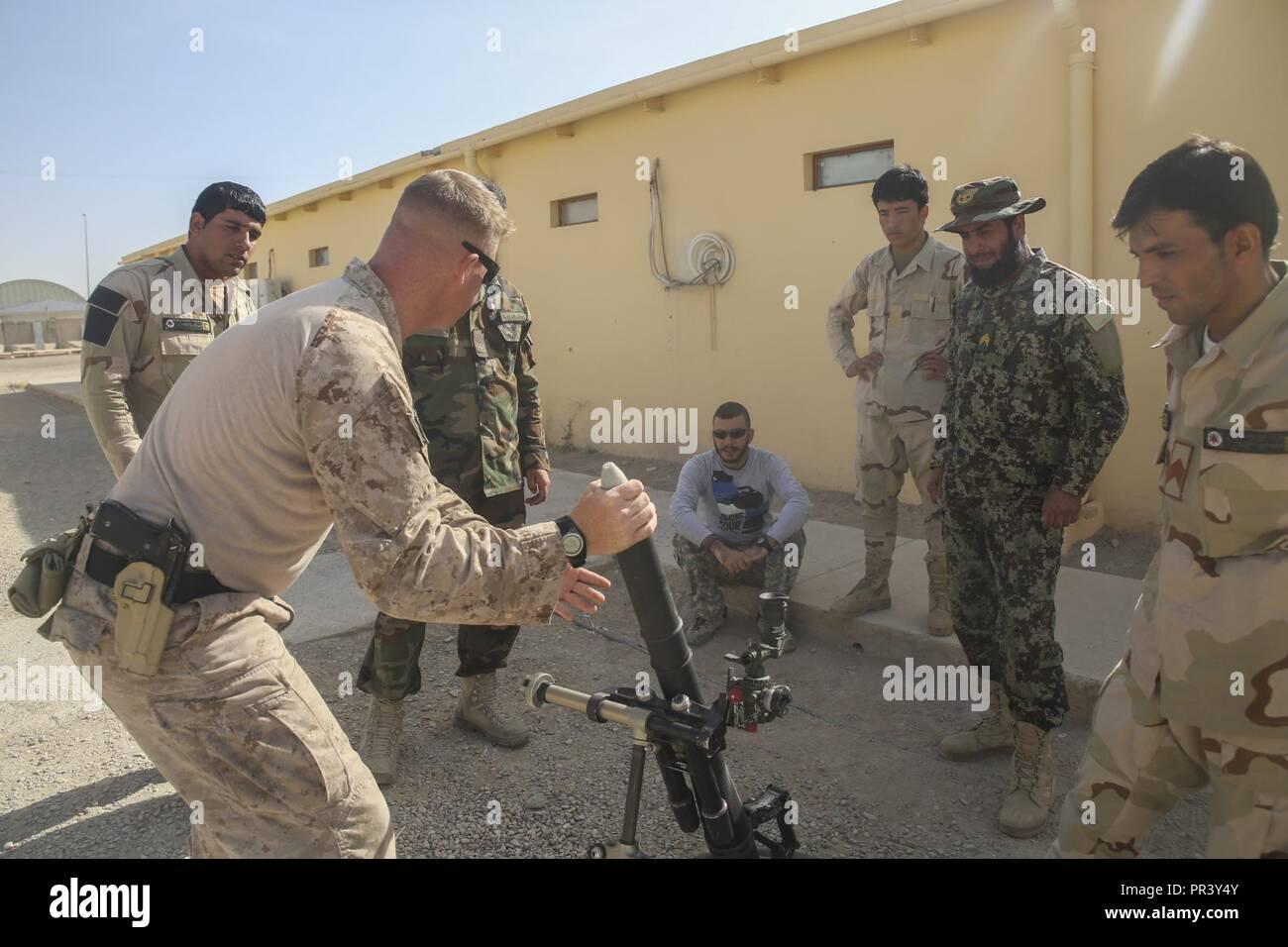Un asesor de Marina de los EE.UU. con Task Force Southwest demuestra buen empleo de un mortero de 60mm a soldados del Ejército Nacional Afgano en la provincia de Helmand Regional Centro de entrenamiento militar en el campamento Shorabak, Afganistán, 31 de julio de 2017. Aproximadamente 50 RMTC instructores están trabajando para mejorar sus habilidades de enseñanza a lo largo de un período de cuatro semanas para formar al formador curso con sus homólogos marinos en preparación de un próximo ciclo de preparación operativa. El ORC es una evolución de ocho semanas de duración centrado en la mejora de las habilidades y técnicas de infantería de ANA soldados. Imagen De Stock