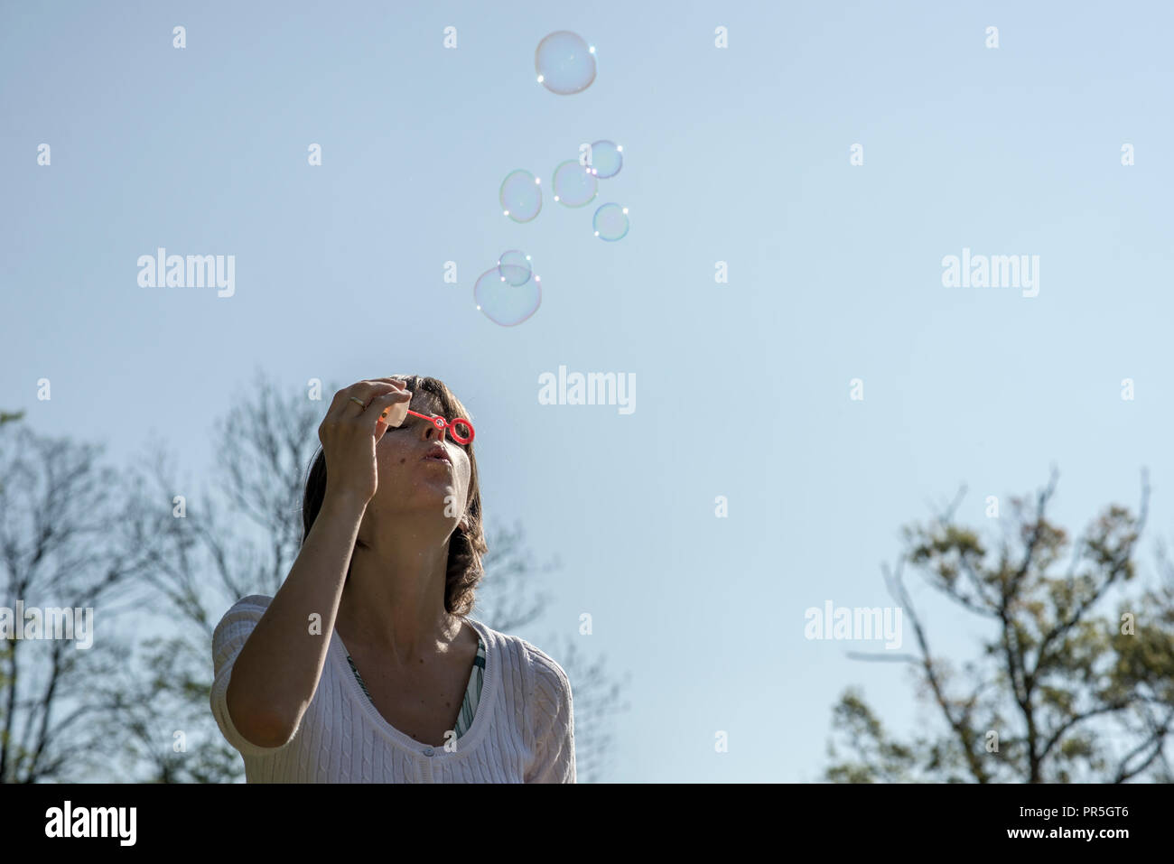 Ninguna mujer en camisa manga corta soplando burbujas fuera con el brillante cielo azul de fondo. Imagen De Stock