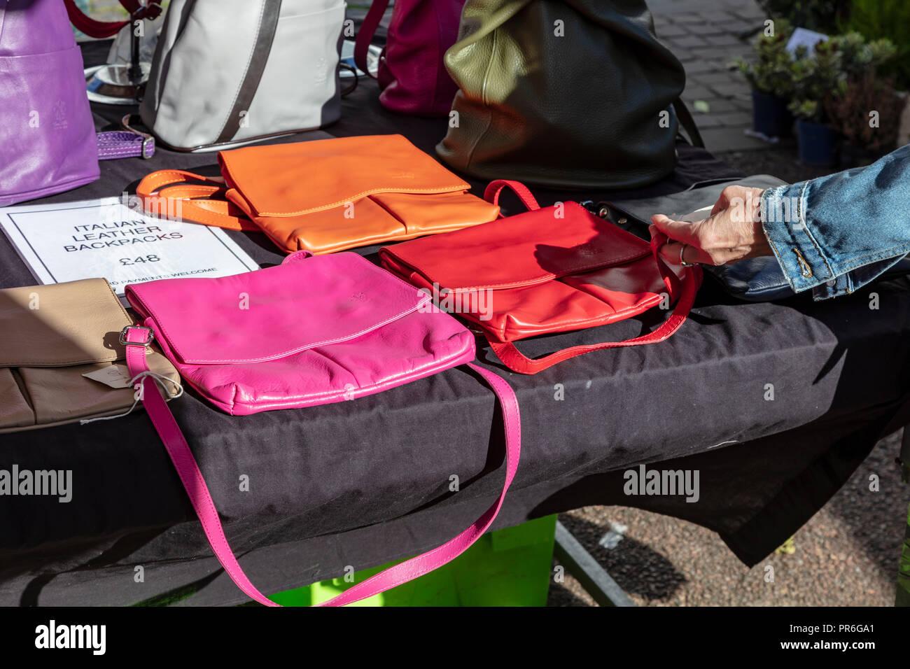 b4d2f1220 Calado en Ludlow mercado de venta de bolsos de cuero italiano y mochilas,  en una colorida exhibición, una mujer toca uno de mano, Ludlow, Shropshire,  RU