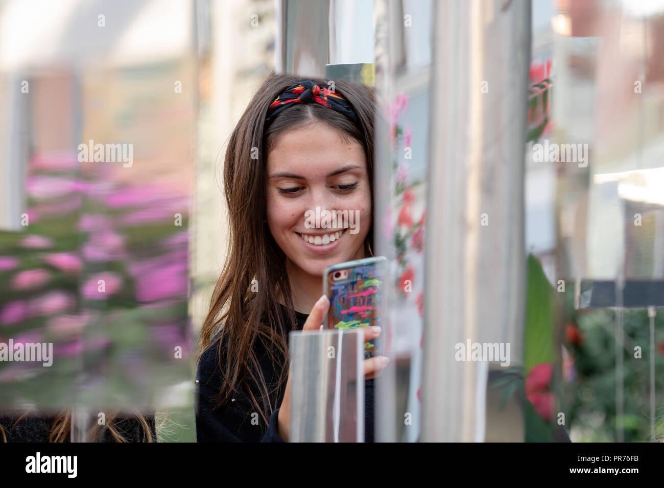 RIGA, LETONIA - 14 de septiembre de 2018: Una joven mira teléfono simplemente fotografiado imágenes. Imagen De Stock