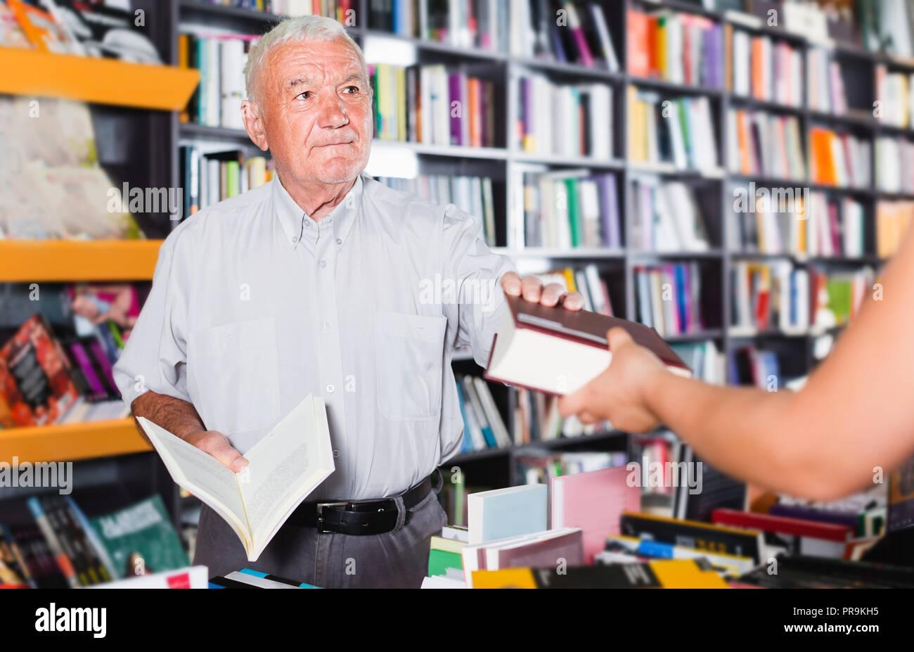 7f4bd1a6a1 Hombre maduro está comprando el libro en la librería Foto & Imagen ...