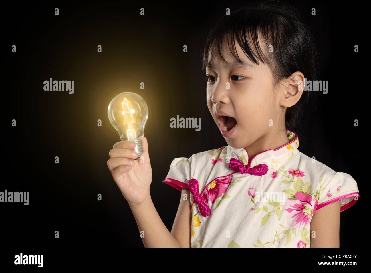 Chino Asia niña la celebración de una bombilla aisladas en fondo negro Imagen De Stock