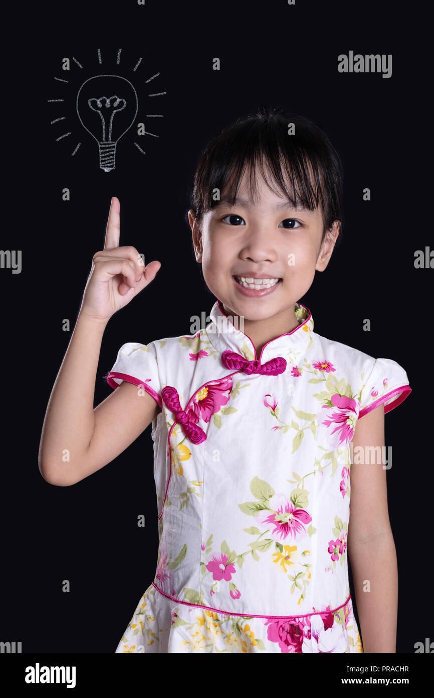 Chino Asia niña dedo hasta la bombilla aisladas en fondo negro Imagen De Stock