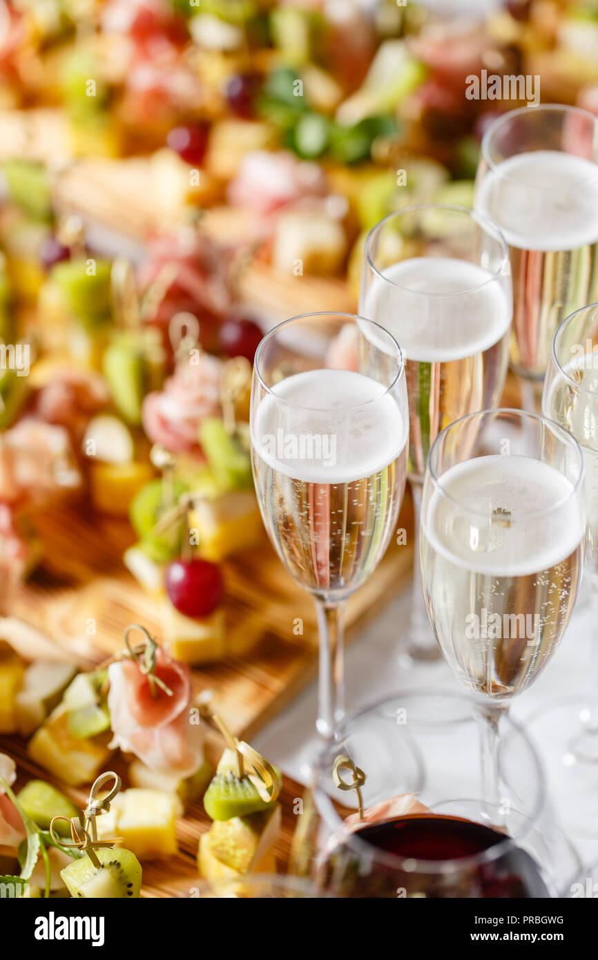 El buffet en la recepción. Copas de vino y champagne. Surtido de canapés sobre la plancha de madera. Servicio de banquetes catering comida, aperitivos con queso, jamón, jamón y fruta Imagen De Stock