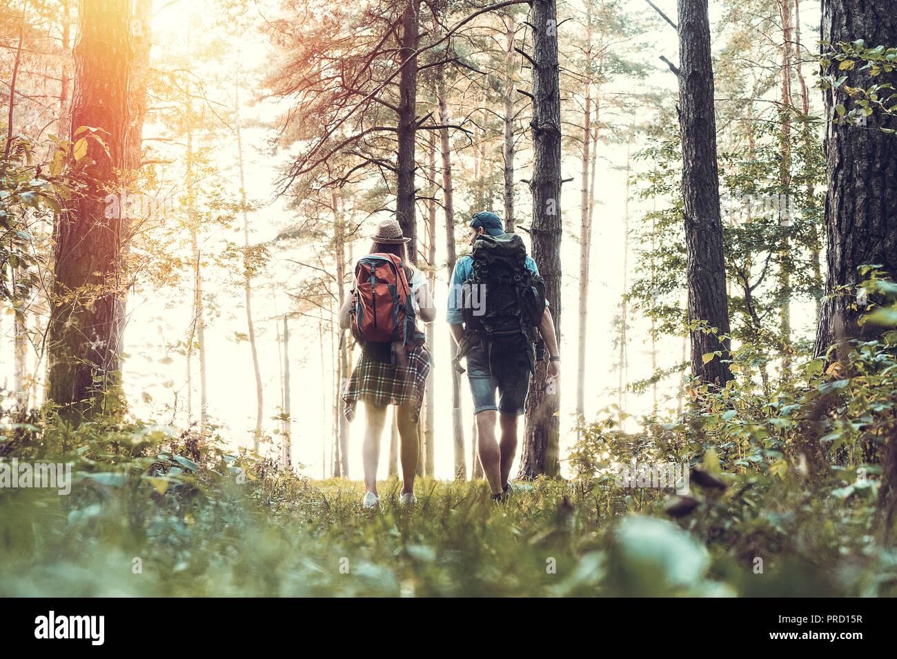 Ruta dura. Hermosa pareja joven senderismo juntos en el bosque mientras disfruta de su viaje. Foto de stock