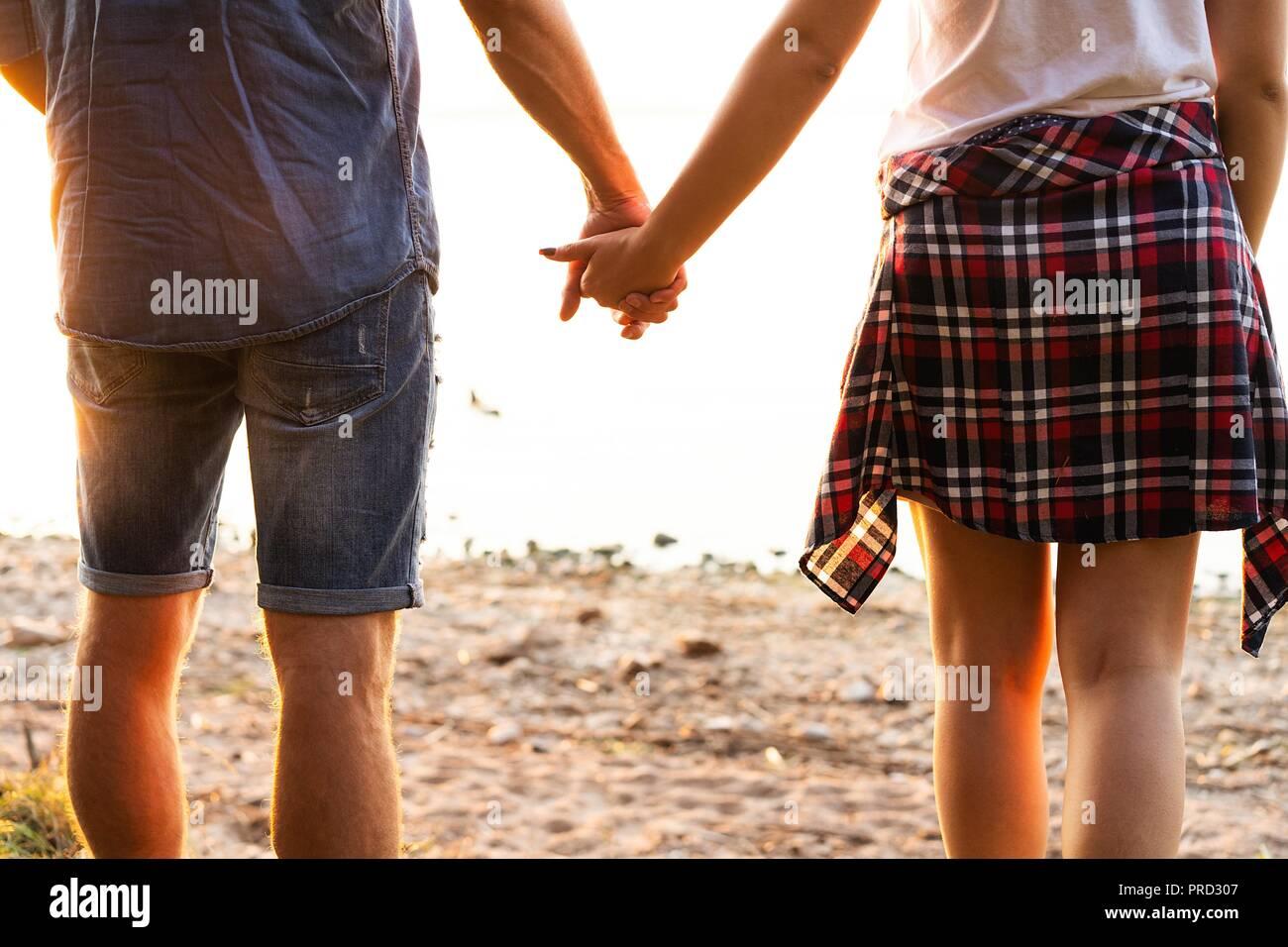 Pareja joven en amor caminando en el parque de otoño manos mirando al crepúsculo. Foto de stock