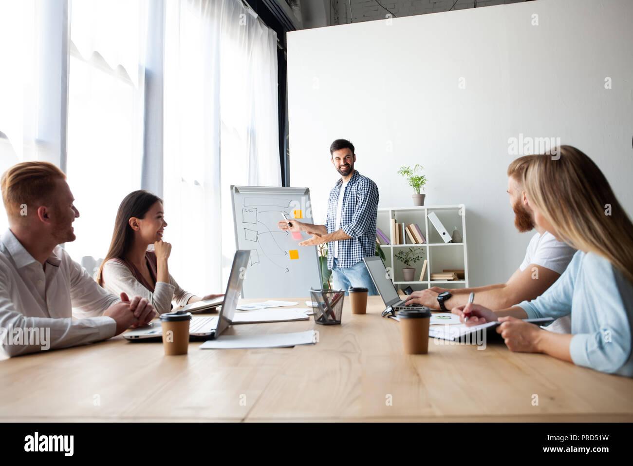 El logro de mejores resultados. Joven contemporáneo realizando una presentación de negocio mientras está de pie en la sala de juntas. Imagen De Stock