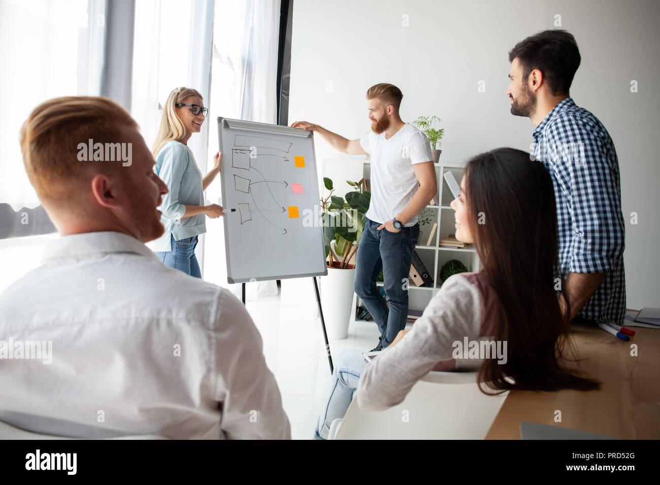 El desarrollo de la nueva estrategia. Dos jóvenes colegas realizando presentación mientras trabaja con su equipo comercial en la oficina. Imagen De Stock
