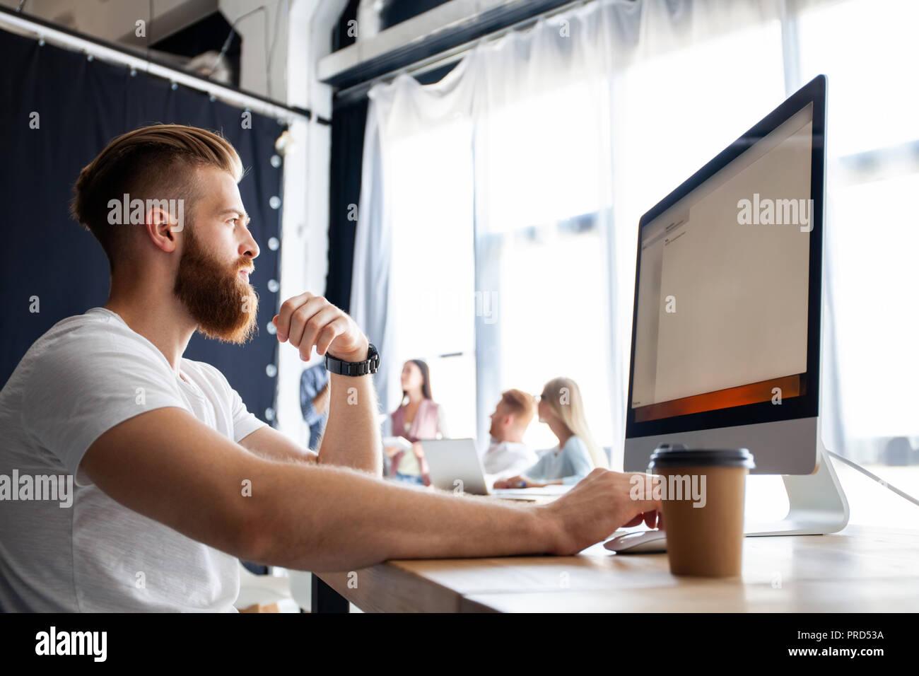 Oficina creativa. Jóvenes colegas moderno en smart ropa casual trabajando mientras pasa el tiempo en la oficina. Imagen De Stock