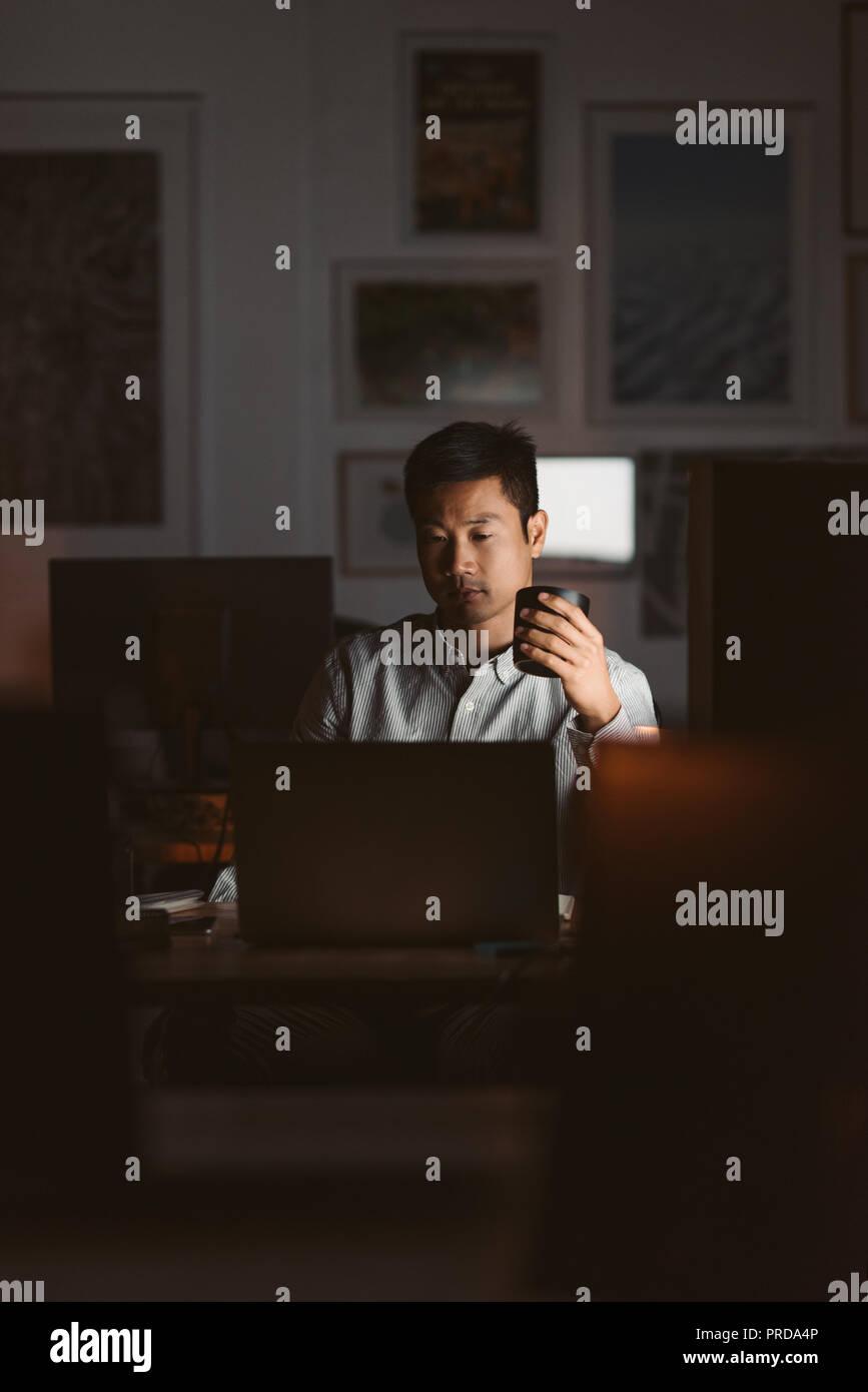 Empresario asiático bebiendo café mientras trabaja en una oficina oscura Imagen De Stock